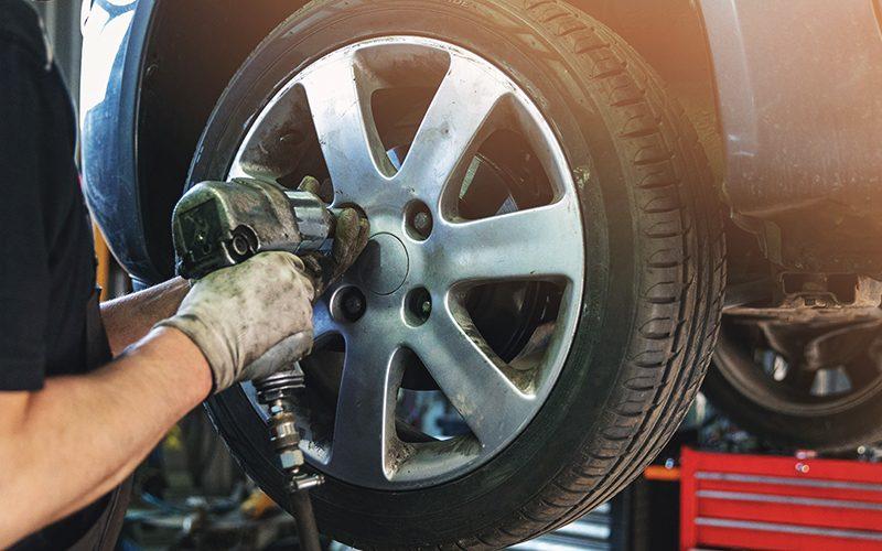car mechanic screwing the wheel at auto repair garage